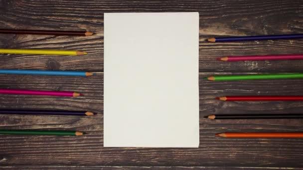 Fehér könyv és színes ceruza a fából készült háttér-stop motion animáció