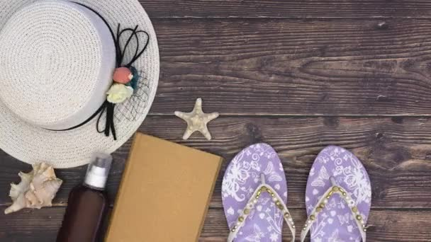 Womans hat slippers and sea shells on the wooden background - Stop motion