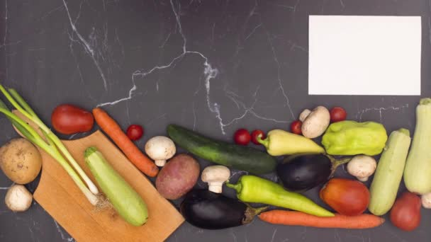 Zastavit animaci čerstvé a organické zeleniny, která se objevuje na kuchyňském stole s řezací desku a bílým papírem k receptu