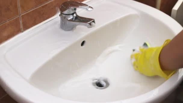 Práce na práci v domácnosti-čištění Koupelnové umyvadla s houbou