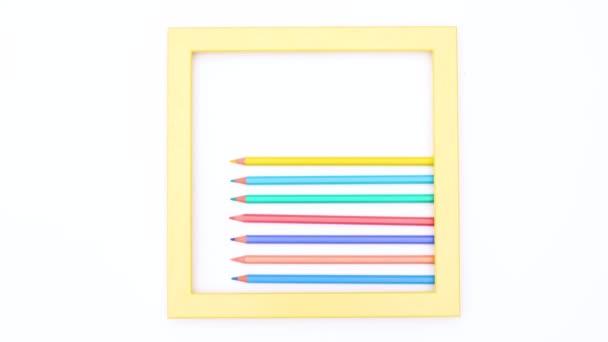 Barevné tužky uvnitř žlutého rámečku s bílým motivem. Zastavit pohyb
