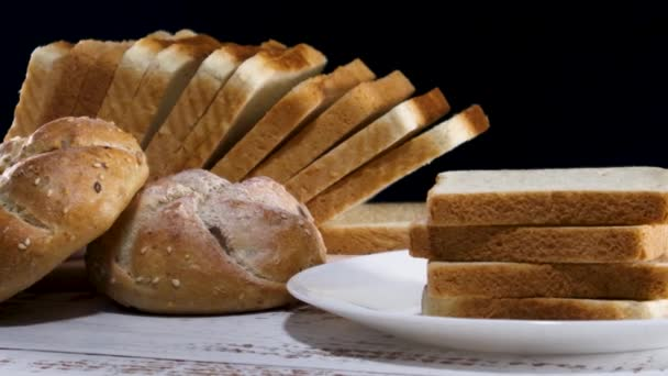Close up of fresh slices of toast bread and two organic buns with sesame on table with kitchen cloth