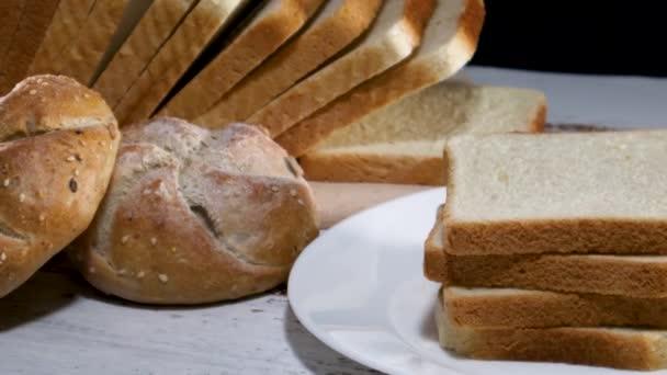 Großaufnahme von frischen Toastbrotscheiben und zwei Bio-Semmeln mit Sesam auf dem Tisch mit Küchentuch