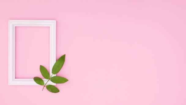 Grünes Blatt und weiße romantische Rahmen auf rosa Thema. Stop-Motion