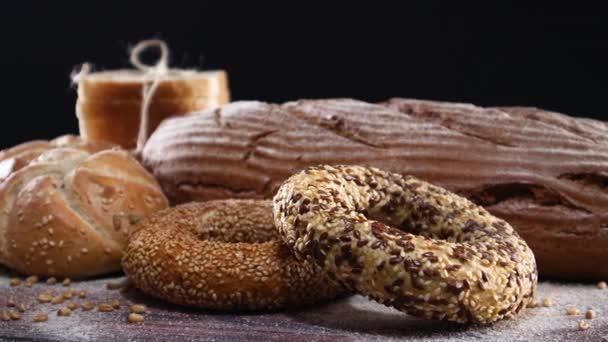Sütőipari termékek, bio rozskenyér, zsemle, bagel fából készült asztalon és fekete téma