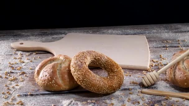 Baker put fresh organic rye bread on cutting board on the table with bun and bagels and flour decoration