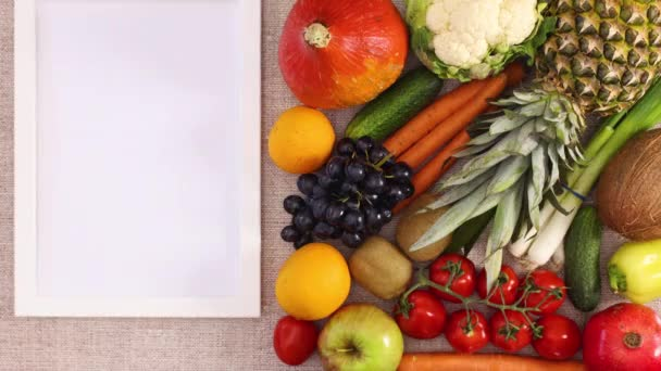 White frame for text, logo or recipe appear next to fresh fruits and vegetables. Stop motion