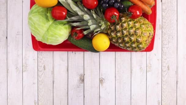 Červený podnos s ovocem a zeleninou se objevuje na lehkém dřevěném motivu. Zastavit pohyb