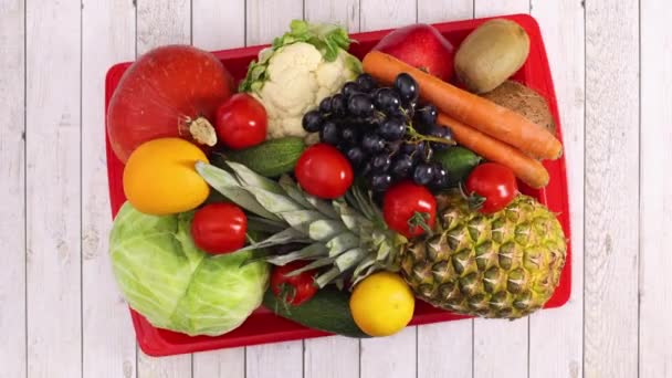 A gyümölcsök és zöldségek piros tálcán mozognak könnyű fa témában. Állj!