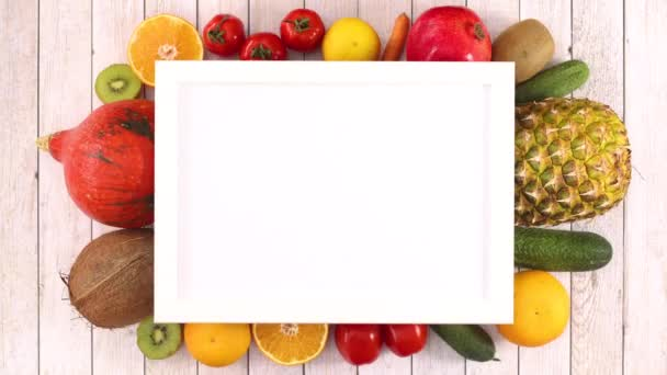 Fresh different fruits and vegetables appear under frame with place for text. Stop motion