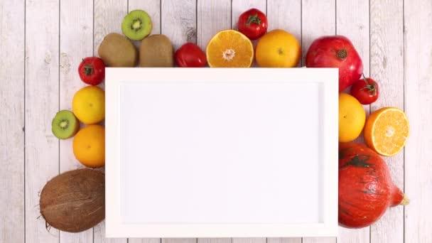 Bílý rám s místem pro text a pohybující se ovoce a zeleninu pod rámem. Zastavit pohyb
