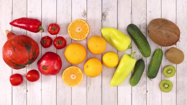 Červené, oranžové, žluté a zelené ovoce a zelenina se pohybují na dřevěné téma. Zastavit pohyb