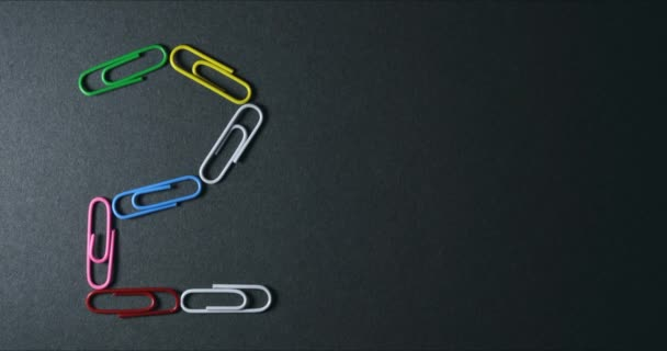 Stop motion of paper clips creaing shapes and symbols