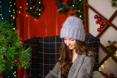portrait of a beautiful girl at christmas. in a knitted sweater and hat. New Year's interior. with long hair wearing warm winter clothes in a Christmas interior. Portrait of a beautiful girl with long