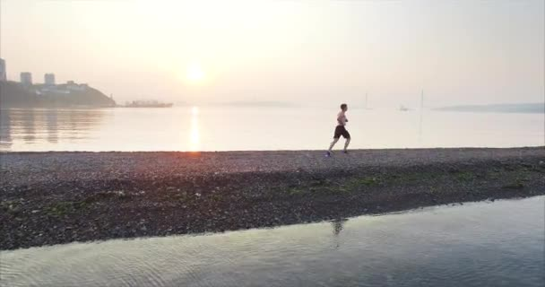 Amazing aerial view of a young man in shorts running at summer sunrise. Camera is following after the sportsman. Tokarevsky spit and lighthouse. Beautiful morning sea. Vladivostok, Russia