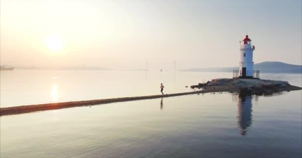 schöne statische Luftaufnahme eines Mannes in kurzen Hosen, der vom Leuchtturm aus schnell die Tokarevsky-Spucke entlang läuft. frisches Morgenmeer bei erstaunlichem Sonnenaufgang. Wladiwostok, Russland