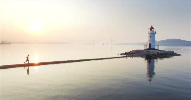 schöne statische Luftaufnahme eines Mannes in kurzen Hosen, der schnell die Tokarevsky-Spucke entlang zum Leuchtturm rennt. frisches Morgenmeer bei erstaunlichem Sonnenaufgang. Wladiwostok, Russland