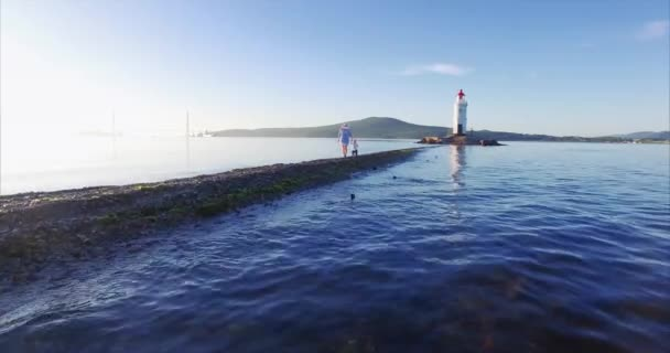 Flying above the water, beautiful aerial view of young mother walking with her toddler son along the spit. Sun is rising above them, warm sunny beams. Russian bridge is on the background. Vladivostok