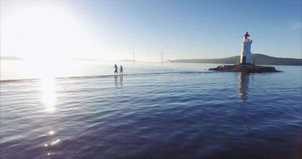 Beautiful view of family walking along spit from Tokarevsky lighthouse. Amazing sea and sunrise. Father holds his wife's hand and his son on shoulders. Vladivostok. Russian bridge is on background