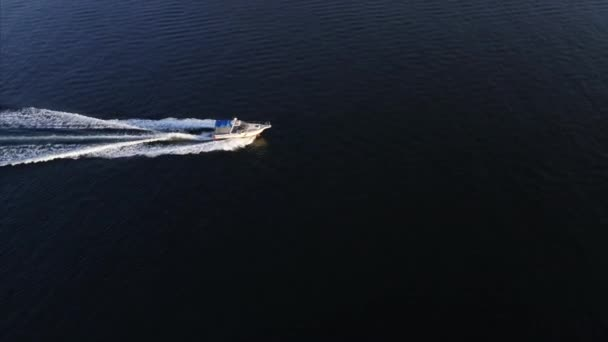 Aerial zooming in view of fast motor lifeboat sailing along the bay