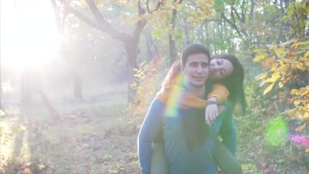 A young woman is on piggy back ride with her boyfriend in sunny autumn forest. They are chatting and smiling