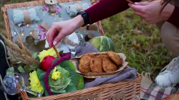 Piknikový košík s piknikovým zbožím, zelím, melounem a květinami. Neznámá žena ho zdobí skořicovými tyčinkami. Podzimní park