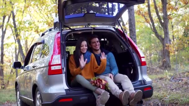 Young man and woman - romantic couple - are having fun, dancing and smiling in car trunk. Sunny autumn wood