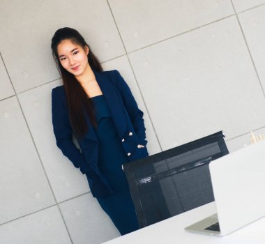 Asian long hair beautiful business woman in navy blue suit smile so happy near her table in modern office.