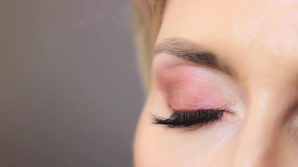 geschlossenes Auge des Mädchens nach dem Auftragen von Make-up auf dem Augenlid von rosa Farbe mit langen schwarzen Wimpern