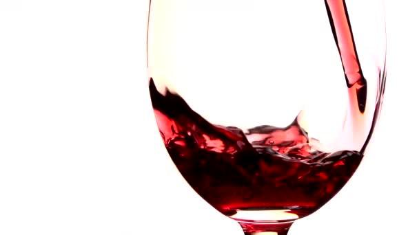 Červené víno nalil do sklenice na bílém pozadí