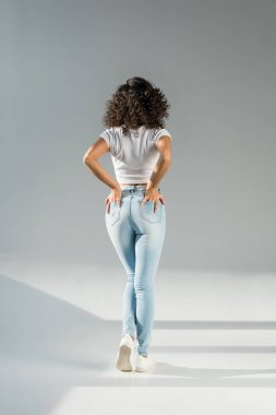 back view of woman standing with hands in pockets in tight blue jeans on grey background
