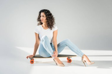 attractive woman with curly hair sitting on skateboard in high heels on grey background