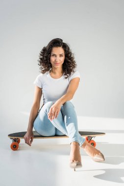 attractive woman with curly hair sitting on skateboard with crossed legs on grey background
