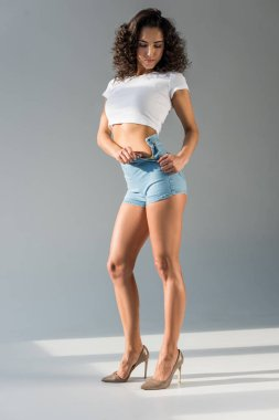 beautiful woman with curly hair unziping lock on blue denim shorts on grey background