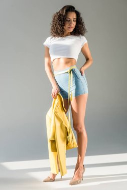 attractive woman with curly hair holding yellow jacket and standing with measuring tape on grey background