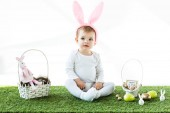 adorable child in bunny ears headband sitting near straw baskets with Easter colorful eggs and decorative rabbits isolated on white