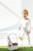 adorable baby standing near straw basket with decorative rabbit on white