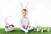 adorable baby in bunny ears headband sitting near straw baskets with Easter colorful eggs and decorative rabbits isolated on white