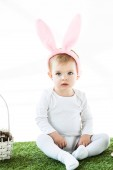 Photo cute dreamy child in bunny ears headband sitting on green grass near straw basket isolated on white