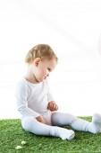 rozkošné blond dítě sedící na zelené trávě izolované na bílém