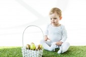 cute child sitting near straw basket with colorful Easter eggs isolated on white