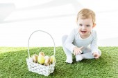 happy child sitting near straw basket with colorful Easter eggs isolated on white