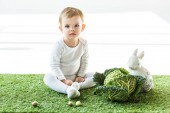 Photo cute baby sitting near savoy cabbage, decorative rabbit and colorful quail eggs on white