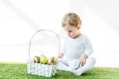 Fotografie adorable child sitting near straw basket with shiny Easter eggs isolated on white