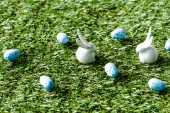 Fotografie decorative rabbits and blue quail eggs on green grass surface