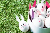 Fotografie chicken eggs with drawn rabbit faces and paper ears on green grass surface