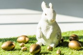 Fotografie decorative Easter rabbit end shiny golden eggs on green grass surface