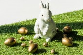 decorative Easter rabbit end shiny golden eggs isolated on grey