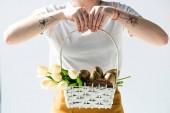 vágott kilátás a nő gazdaság szalma kosár arany húsvéti tojást és tulipán elszigetelt fehér