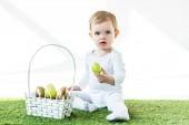rozkošný kluk držící žluté kuřecí vajíčko, když sedí nedaleko slamáku s Velikonocemi na bílém